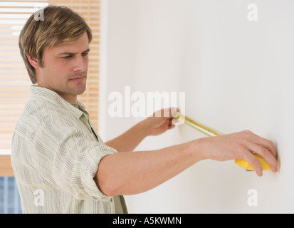 Man measuring wall with tape measure - Stock Photo