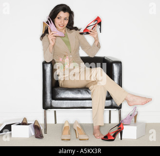 Woman comparing shoes at shop - Stock Photo