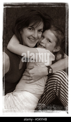 A mother holds her young daughter playfully and affectionately in this black and white portrait with a brushed edge - Stock Photo