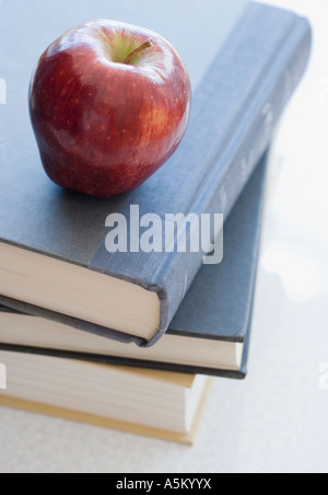 Close up of apple on stack of books - Stock Photo