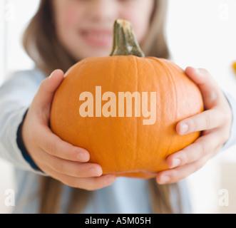 Close up of girl holding pumpkin - Stock Photo