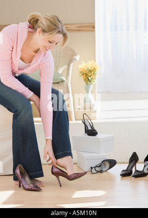 Woman trying on shoes in shop - Stock Photo