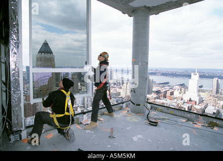 Workers,  with safety harness unclipped, installing curtain wall at Random House building in New York City - Stock Photo