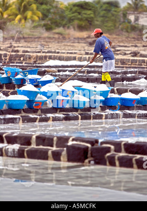 Lady loading salt into containers in the rain - Mauritius - Stock Photo