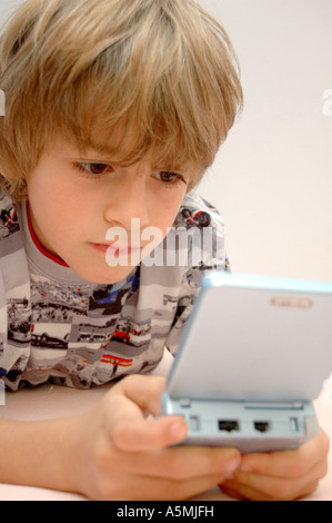 Junge spielt am Gameboy boy playing with Gameboy Kind Menschen Mensch Personen Leute people jung kindlich Kinder - Stock Photo
