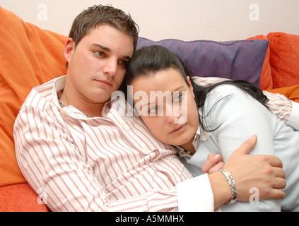 Junges Paar kuschelt auf der Couch young couple cuddle on couch Paar Menschen Mensch Leute Person Personen Paar - Stock Photo