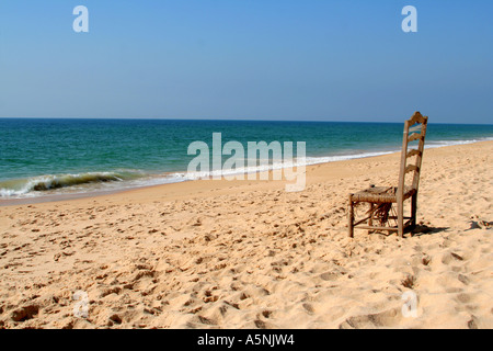 single ragged and tattered old chair on a deserted beach Faro Algarve Portugal - Stock Photo