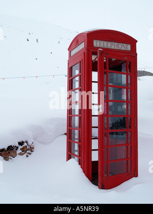 Old fashioned red telephone box K6 with door open in deep winter snow on Cairngorm mountain Cairn Gorm Highland - Stock Photo