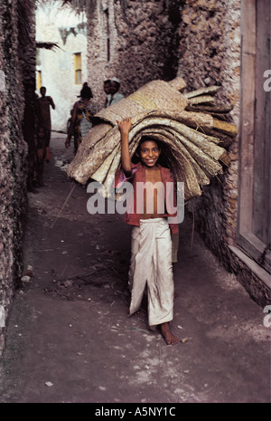 Young boy carrying mats Pate Island Lamu archipelago Kenya coast East Africa - Stock Photo