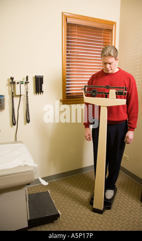 Man weighing himself in physician's exam room. - Stock Photo