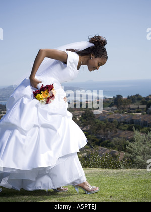 Profile of a bride holding a bouquet of flowers and looking at her shoes - Stock Photo