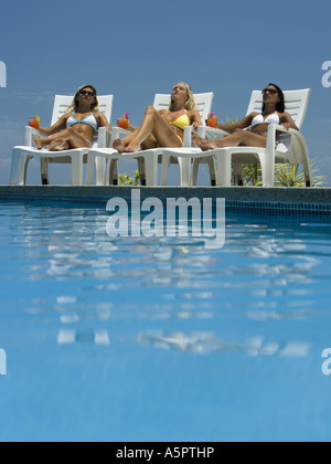 Three young women sunbathing by the pool - Stock Photo