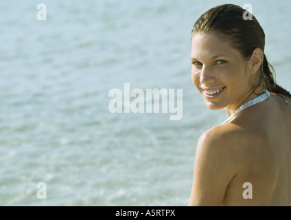 Young woman on beach, looking over shoulder at camera