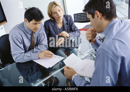 Professional couple having meeting with businessman, discussing documents - Stock Photo