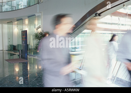 Business executives walking in lobby, blurred motion - Stock Photo