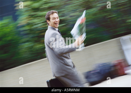 Businessman carrying bouquet of flowers - Stock Photo