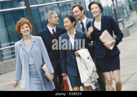 Group of business executives walking in business park - Stock Photo