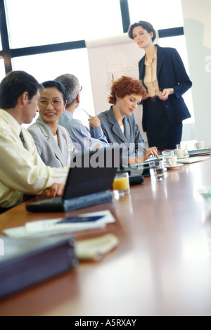 Group of businesspeople sitting around conference table during presentation - Stock Photo