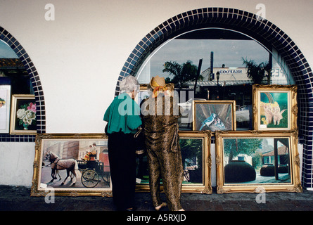 CUBAN EXILE COMMUNITY MIAMI STREET SCENE OF MIAMI S LITTLE HAVANA AN OLD COUPLE LOOKING AT PAINTINGS - Stock Photo