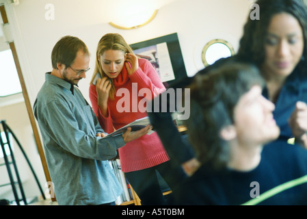 Man and woman looking at catalog, second man and woman in foreground - Stock Photo