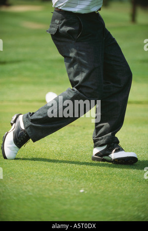 Golfer in mid swing, low section - Stock Photo