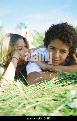 Boy and girl lying in grass - Stock Photo