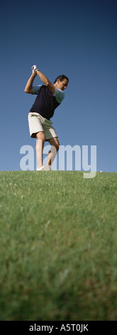Golfer swinging, low angle view - Stock Photo