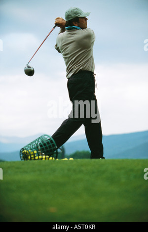 Golfer practicing on driving range, low angle view - Stock Photo