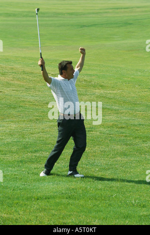 Golfer standing with arms in the air, full length - Stock Photo