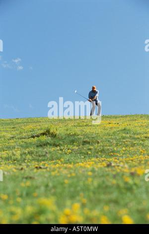 Golfer swinging, wildflowers in foreground - Stock Photo