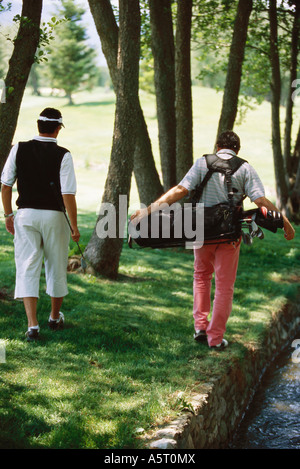 Golfers looking for ball under trees, rear view - Stock Photo