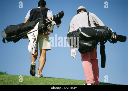Golfers carrying golf bags, rear view - Stock Photo