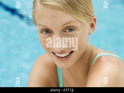 Young woman smiling, portrait, pool in background - Stock Photo