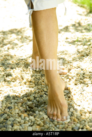 Woman taking step, barefoot on gravel, knee down - Stock Photo