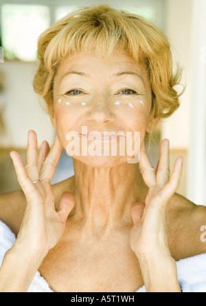 Senior woman applying moisturizer - Stock Photo