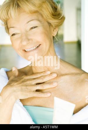 Senior woman applying moisturizer to chest - Stock Photo