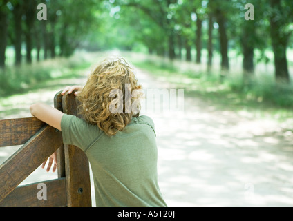 Boy leaning against wooden gate, facing dirt road, rear view - Stock Photo