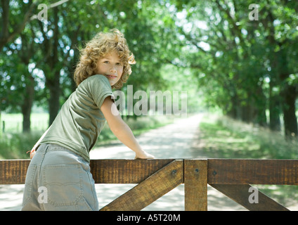 Boy leaning against wooden fence, looking over shoulder at camera - Stock Photo