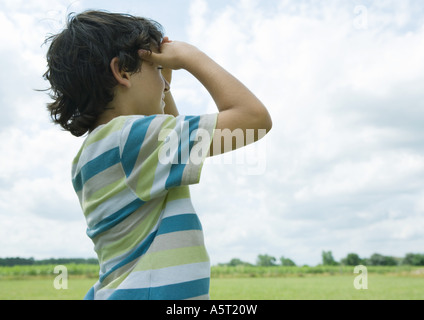 Boy shading eyes, looking into distance - Stock Photo