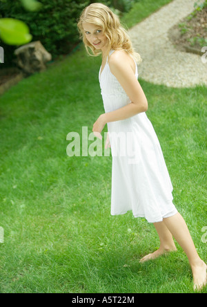 Young woman standing in yard, wearing sundress, smiling at camera - Stock Photo