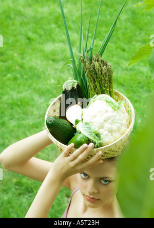 Woman holding basket full of fresh vegetables on top of head - Stock Photo