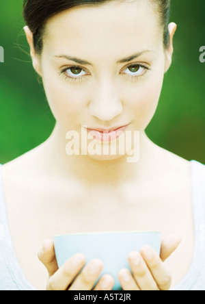 Woman holding bowl in hands, looking at camera - Stock Photo