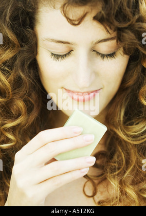 Woman smelling bar of soap - Stock Photo