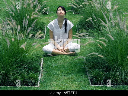 Woman sitting in ornamental garden with eyes closed - Stock Photo