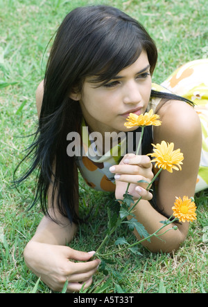 Woman lying on grass, smelling flower - Stock Photo