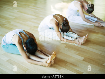 Yoga class, women doing seated forward bend - Stock Photo