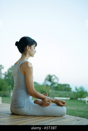 Woman sitting in lotus position - Stock Photo