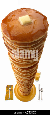 Very high pancake stack on yellow plate with flatware orange juice etc  - Stock Photo
