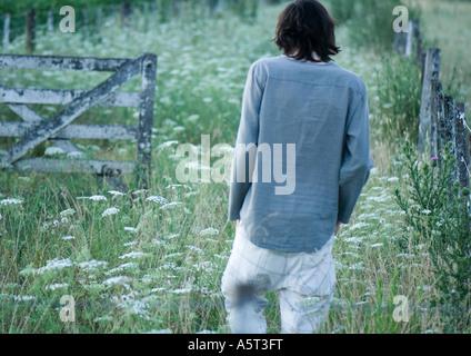 Man walking in field, rear view - Stock Photo