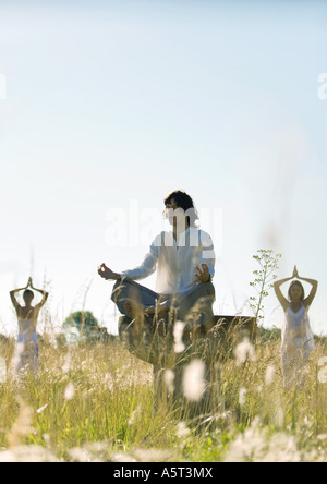 Young adults doing yoga outdoors - Stock Photo